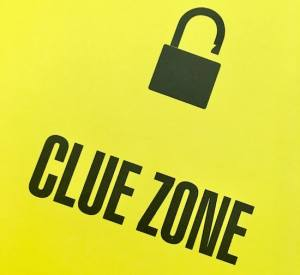 """In-book, page reads, """"Clue Zone"""" with an unlocked padlock."""