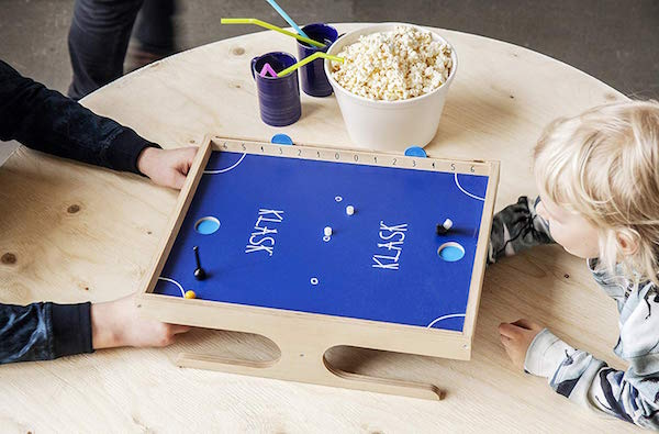 Two kids reaching under the Klask table to play it.