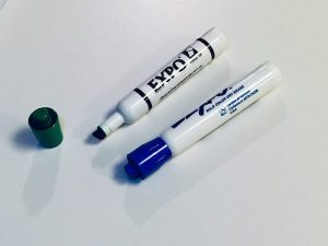 Dry erase markers on a whiteboard.