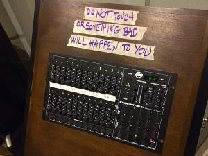 "A mixing board that is messily labeled, ""DO NOT TOUCH OR SOMETHING BAD WILL HAPPEN TO YOU."""