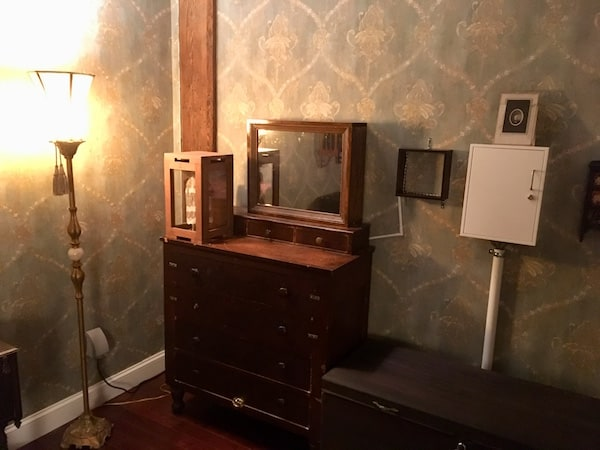 In-game: An old apartment bedroom's dresser. There are metal boxes with wires running from them.