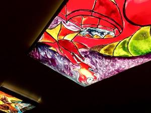 In-game: a stain-glass window depicting a fire-breathing dragon.