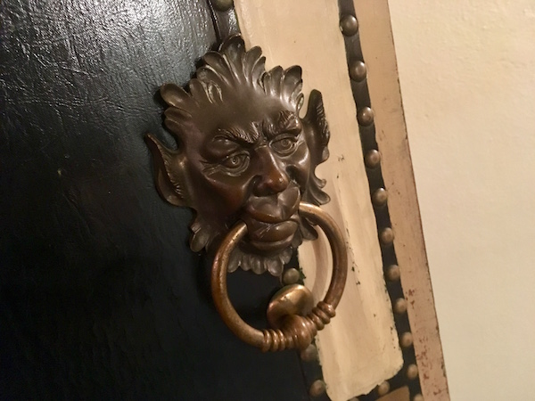 In-game: Close-up of a door handle that looks demonic.