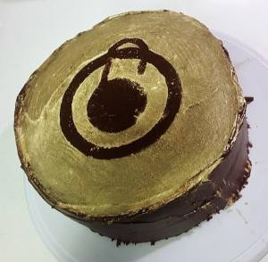 A large chocolate cake dusted in gold with the outline of the golden lock-in award in the negative space.