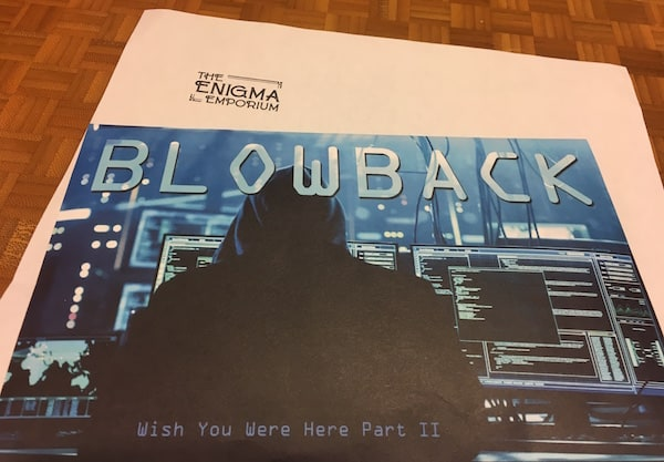 "The ""Blowback: Wish You Were Here Part II"" envelope depicts a black hoodied hacker in front of many computer monitors."