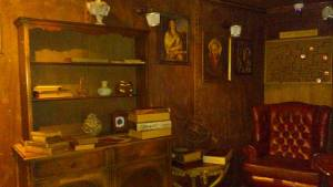 In-game: an old study-like environment with books, paintings, a large red leather chair, and a maze.