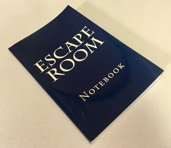 "The cover of the navy blue journal reads, ""Escape Room Notebook"""