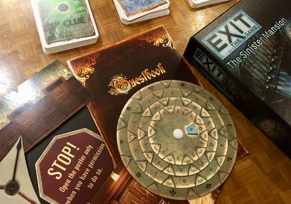 An assortment of game components, an answer disk, a booklet, a map, and 3 decks of cards.