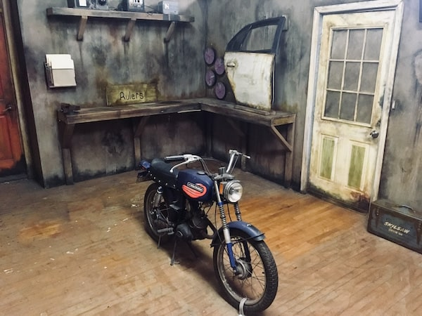 In-game: Wide angle shot of The Garage, a small motorcycle sits in the middle of the room, a car door rests on a workbench in the background.