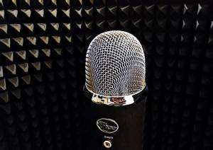 A blue yeti microphone surrounded by a sound absorbing shield.