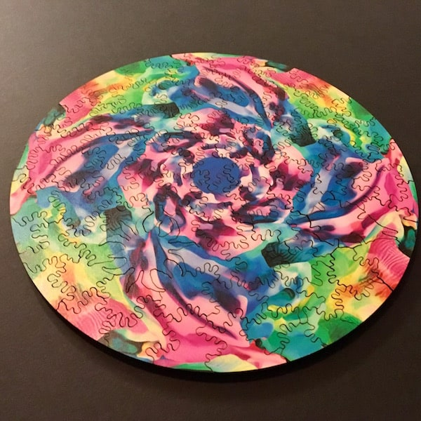 The colorful, circular, assembled puzzle.