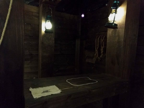 In-game: A table with a map on it inside of a lantern-lit pirate ship.