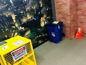 "In-game: A yellow cage labeled ""flammable materials"" a garbage can, an orange traffic cone, and an oversized wall decal of a screenshot from the Batman from Arkham Knight video game."
