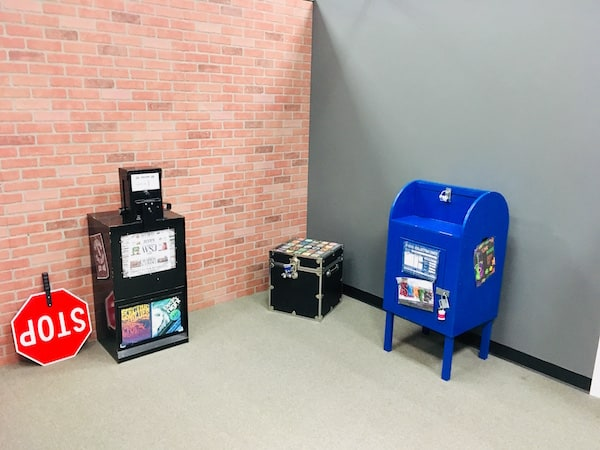 In-game: A brick facade, a newspaper vending machine, a handheld stop sign, a blue mailbox.