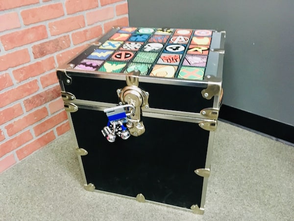 In-game: A trunk with 20 super hero logos on the top, sealed with two combination locks.