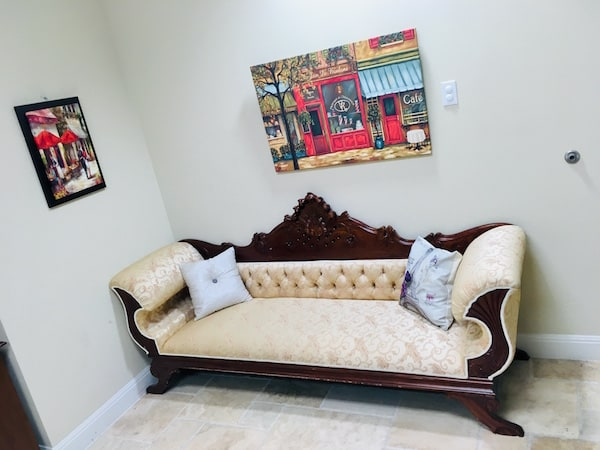 In-game: An antique white couch in a white room with paintings of France hanging on the walls.