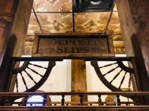 """In-game: A sign that reads, """"Deposit Slips"""" surrounded by intricate woodwork, above it is a beautiful gold ceiling."""