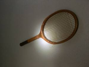 In-game: A racket hanging on the wall in a dark room.