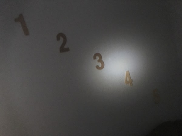 In-game: The numbers 1 through 5 hanging diagonally on the wall of a dark room.