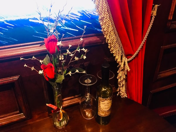 In-game: A vase with roses, two wine glasses, and a bottle on a table before a window with a snow storm beyond it.