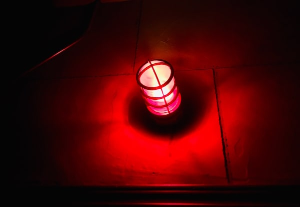 In-game: Closeup of a glowing red light in a dark room.