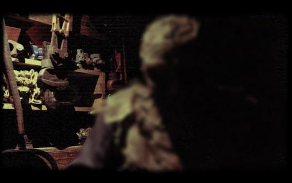 In-game: a menacing hooded man in a workshop.