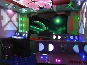 In-game: The bridge of a space ship with multiple control consoles and many glowing lights.
