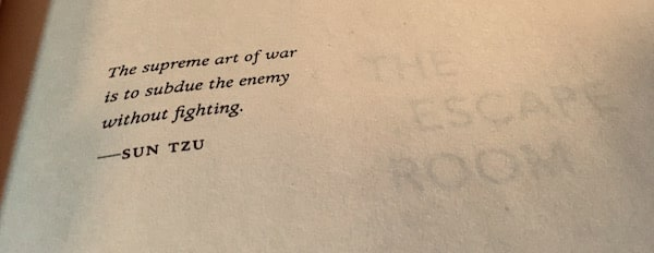 "The title of ""The Escape Book"" bleeding through from the next page beside a Sun Tzu quote, ""The supreme art of war is to subdue the enemy without fighting."""