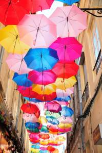 Many umbrellas open and hovering between buildings.
