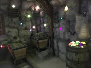 In-game: A gem mine with mining carts, and gems protruding from the walls and ceiling.