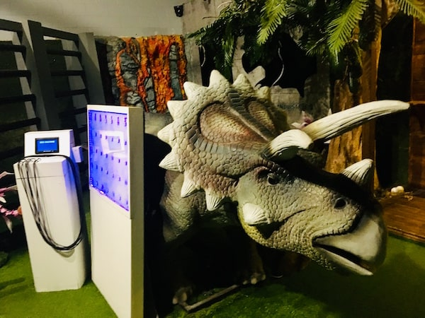 In-game: a triceratops next to a white and blue medical scanning device.
