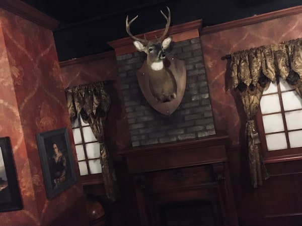 In-game: An elegant study with red and wood walls. The trophy of a buck hangs over a fireplace.