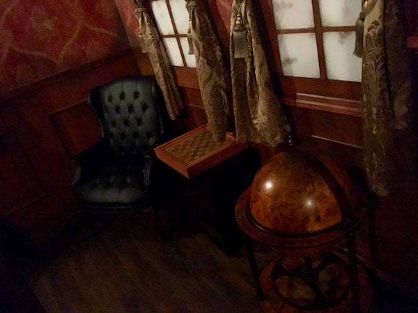 In-game: A chair beside a chess table and a globe in a study.