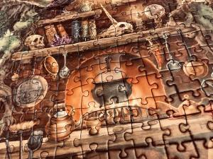 Portion of an assembled jigsaw puzzle featuring a kettle over a fire surrounded by magical ingredients and books.