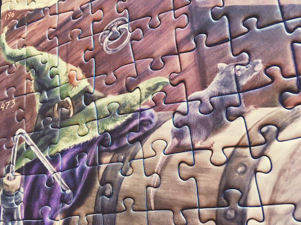 Portion of an assembled jigsaw puzzle featuring a a witch's hat and a rat.