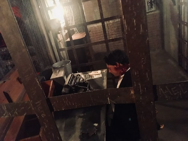In-game: A dead man sitting at a desk with a typewriter in betwen two jail cells.