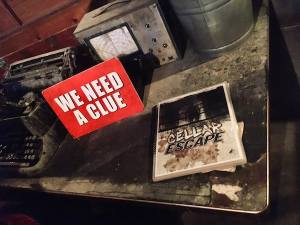 """In-game: A red we need a clue sign sitting beside a laminated and spiral-bound book labeled """"CELLAR ESCAPE."""" All surrounded by a beautiful set."""