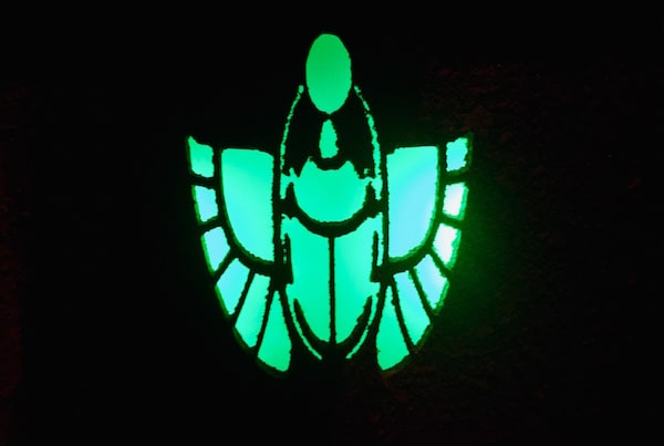 In-game: A glowing green scarab image in darkness.
