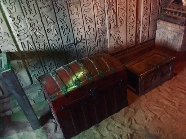 In-game: A treasure chest, and small locked wooden box sitting on top of sand with hieroglyphs adorning the wall behind them.
