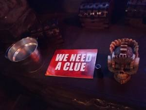 """In-game: A bright """"we need a clue"""" sign beside a flashlight, an ornate skull, and many small treasure chests."""