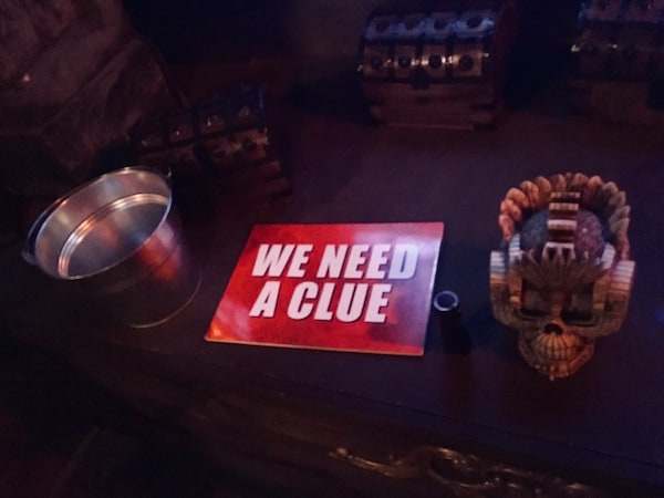 "In-game: A bright ""we need a clue"" sign beside a flashlight, an ornate skull, and many small treasure chests."