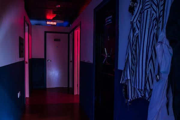 In-game: The hallway of an asylum with patient clothes hanging from hooks on the wall with the lights turned down.