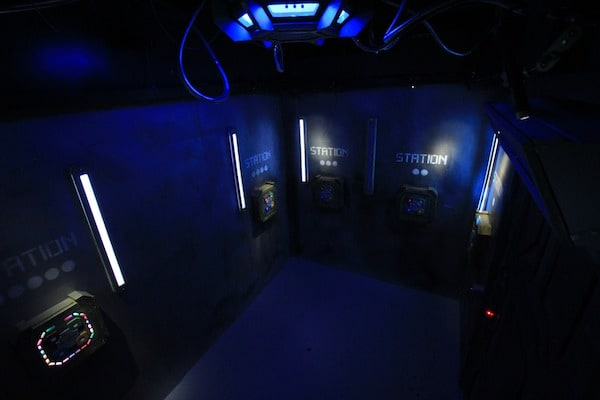 In-game: Wide angle shot of a room with access terminals along the walls.