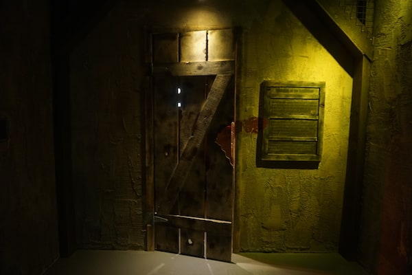 In-game: A worn wooden door with a bloody handprint beside it.