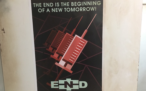 "In-game: A poster of needles labeled, ""The end is the beginning of a new tomorrow!"""