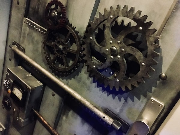 In-game: The interior of a heavy metal vault door. Large gears and a locking bolt in view.