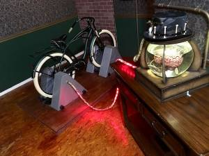 In-game: A brain in a jar hooked up to a bicycle by a glowing red cable.