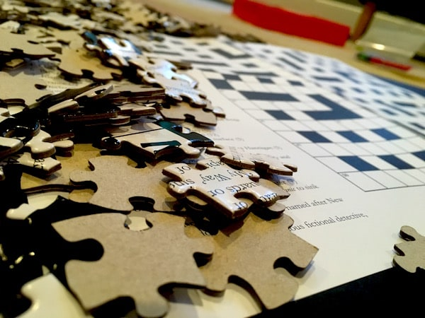 A pile of jigsaw pieces beside a crossword puzzle.