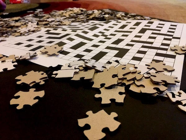 Jigsaw pieces scattered around a crossword puzzle.