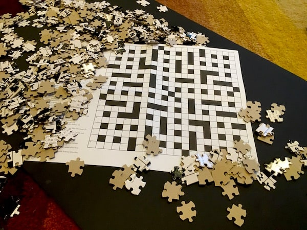 Loose jigsaw pieces surrounding a paper crossword puzzles.